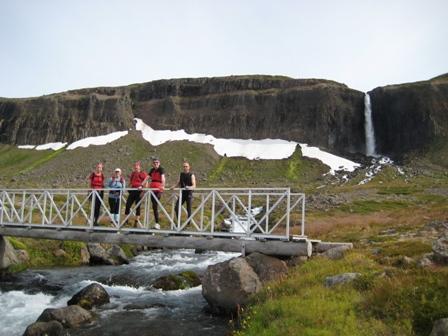 Á göngubrúnni yfir Innraskarðsá á Snæfjallaströnd. Möngufoss í baksýn.