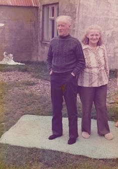 Pabbi og mamma fyrir utan húsið í Gröf, líklega sumarið 1977. Mottuna sem þau standa á heklaði mamma úr trollgarni og hafði hana lengi fyrir forstofumottu bakdyramegin.